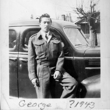 George SL Wong stands next to car. Likely shot in Canada circa 1943.