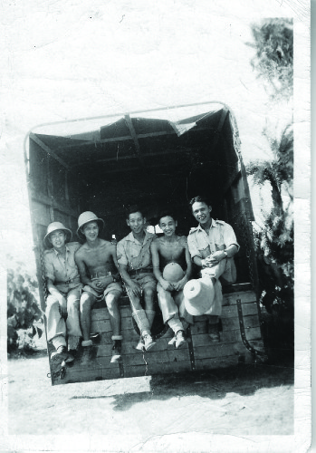 Force 136 recruits relax in the shade of a lorry/truck in India